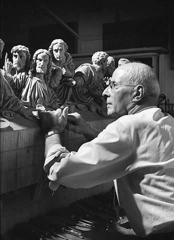 """Alois Lang, master woodcarver, working on """"The Last Supper"""" in 1942 from his studio in Grand Rapids, Michigan (where American Seating had relocated). Lang was in his 30s (in 1919) when he carved the two statues for Augustana Sioux City."""